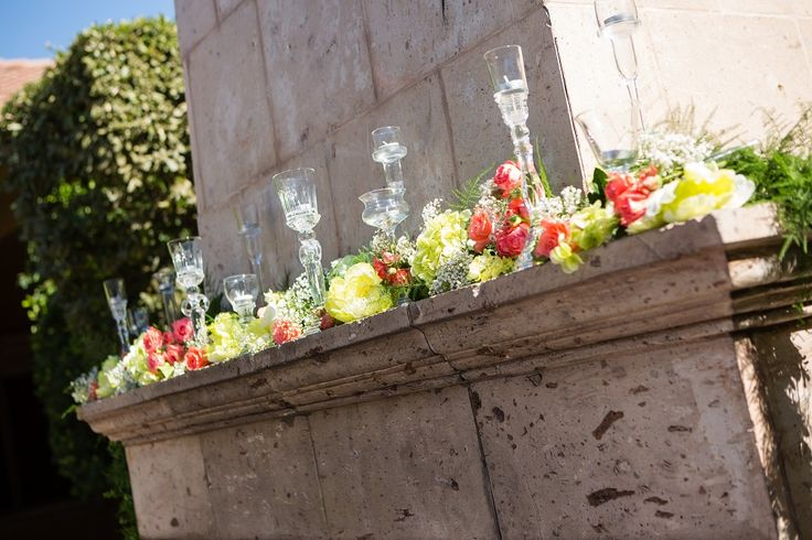Outdoor fireplace mantel with coral and green flowers with tall glass candle holders sitting on top | David De Dios Photography | villasiena.cc