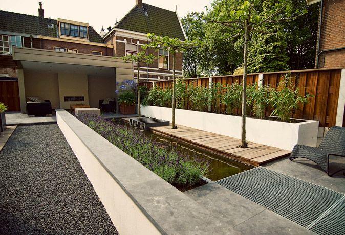 Smalle strakke stadstuin / kleine tuin met zeer mooie details. Let op het natuursteen dat vanuit het terras over de wit gestuukte muur door loopt en de  3 kleine watervallen die in de vlonder zijn verwerkt.