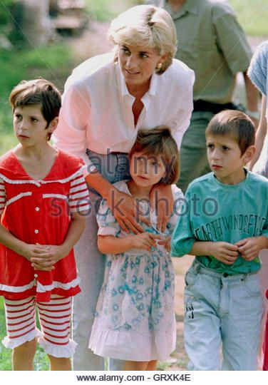 Britain's Princess Diana poses with the children of landmine victim Muhamed SoljankicAugust 9 in the northeastern town of Tuzla. From left to right are;  Muhamed's daughters Merima and Nasiha followed by their son Becir. The princess brought Muhamed Soljankic, injured in a mine blast during the Bosnian war, a birthday cake for his 38th birthday. Diana is touring Bosnia to highlight the plight of landmine victims. - Stock Image