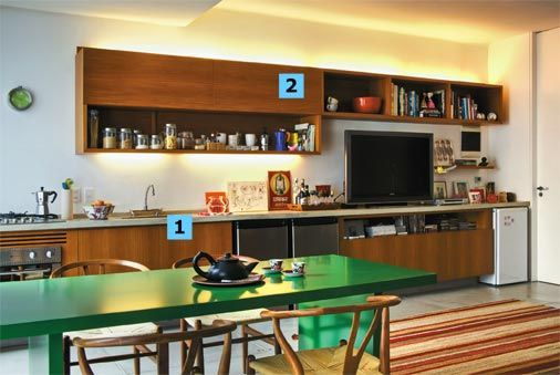 1. Bancada contínua: moldada como uma laje de concreto, ela tem 3,15 m de extensão e segue da cozinha à sala de estar. Para executar essa prancha, uma fôrma de madeira com as furações previstas (cooktop, torneira, cuba e fiação elétrica) recebeu os vergalhões e o cimento. Foi engastada na parede (2 cm) e tem o apoio de quatro muretas de alvenaria (5 cm de espessura) escondidas pela marcenaria. O revestimento é tecnocimento na cor areia protegido com resina (ambos da NS Brazil).2. Contorno…