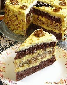 Tort cu nuci, stafide si bezea ~ Blat de bezea:  3 albusuri de ou 120 g zahar 100 g nuci pisate 60 g stafide 50 ml rom (pentru stafide) 3 linguri de faina  Pentru crema de vanilie: 3 galbenusuri de ou 150 g zahar 2 plicuri zahar vanilat 2 plicuri pudding de vanilie 700 ml lapte  250 g unt 200 g zahar pudra