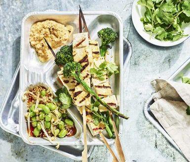 Omtyckt vegetariskt recept på grillade tofuspett med en sataysås på jordnötter och sambal oelek. Servera med grillad bellaverde-broccoli och en röra av marinerade bönor.
