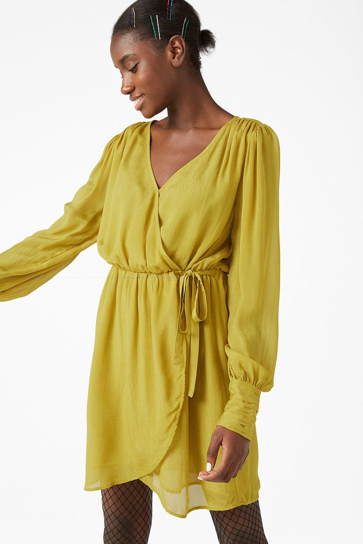 <p>This vintage-inspired wrap dress is gold in so many ways. Gathered, puffed sleeves with vintage cuffs, an asymmetrical hem and hidden double buttons to k