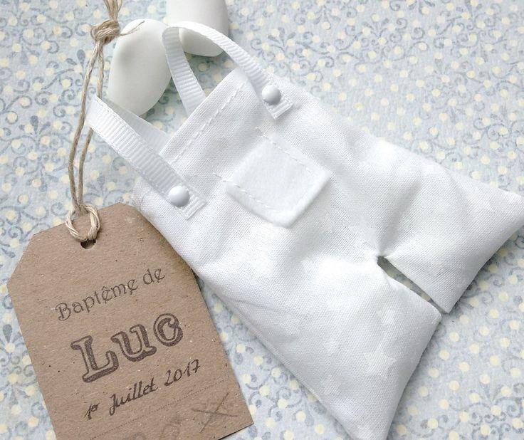 Cette petite salopette en coton blanc est un joli cadeau à offrir à vos invités lors du baptême de votre bébé. Il peut être assorti au faire part petite salopette n°23 que vous retrouverez sur ma boutique Envie dA. Il est composé : - dune petite salopette en coton blanc avec étoiles
