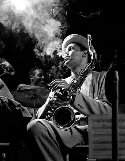 I like the light in this photograph of a jazz musician because he is lit only from above. Liting people from above gives them a holy-quality. The smoke and reflection off of his saxaphone adds to the lighness of the picture.