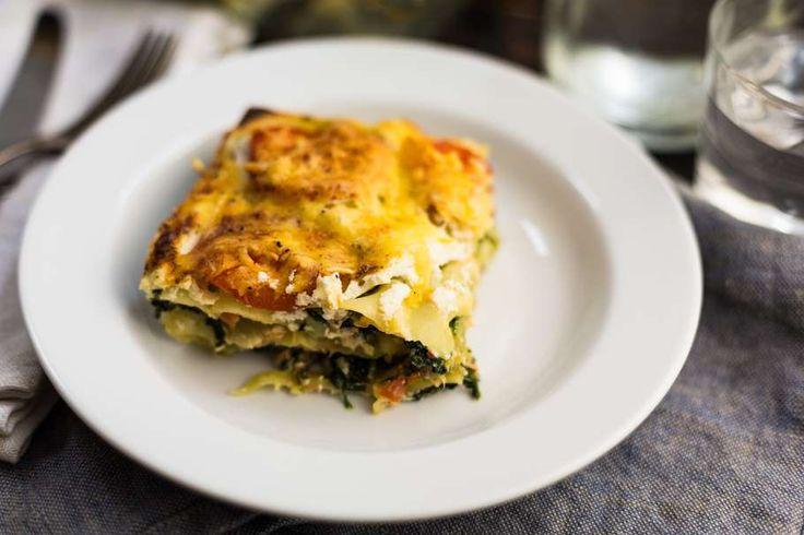 Recept voor zalmlasagne voor 4 personen. Met zout, olijfolie, peper, verse spinazie, ricotta, lasagnebladen, geraspte kaas, gerookte zalmfilet, ui, melk en tomaat