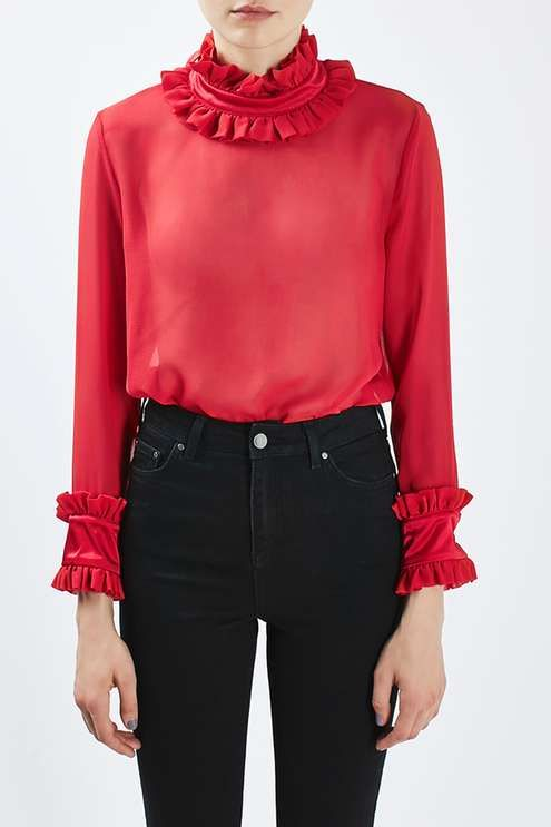 Exude modern glamour in this victoriana inspired sheer gorgette blouse with ruffle detailing at the cuff and neck. In a luxe red hue, this blouse is best worn with black jeans or trousers for a chic contrasting finish