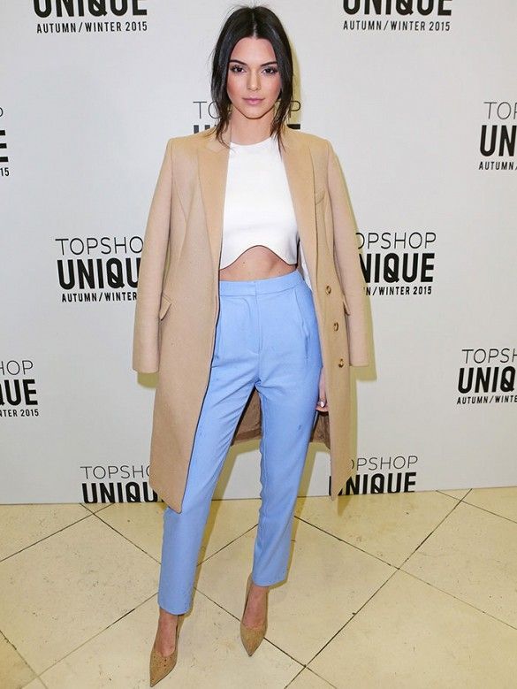 Kendall Jenner wears a white crop top, camel coat, pastel blue trousers, and nude pumps
