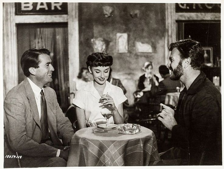Written by John Dighton and Dalton Trumbo, Roman Holiday is a 1953 American romantic comedy film directed and produced by William Wyler. Pictured are Audrey Hepburn, Gregory Peck and Eddie Arnold.