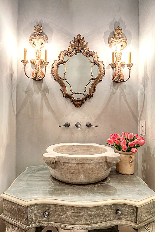 Antique vessel sink and vanity, sconces, and mirror.