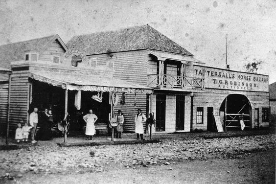 Ruthven Street, Toowoomba, ca. 1873 - Ruthven Street showing a number of business premises. The names of the stores facing the street are visible and clearly identify the following buildings: R. J. Barry's Saddlery, Tattersall's Horse Bazaar, and T. G. Robinson Auctioneer. A group of people including shopkeepers stand outside the buildings.
