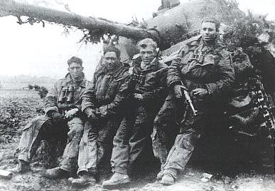 Cpl. Blackie Levers and crew of C-Sqdr. South Alberta Regiment, Royal Canadian Armoured Corps, after their tank was knocked out by a Teller mine. Taken in NE Holland in 1944, Levers holds a 'liberated' German MP40 Machine Pistol.