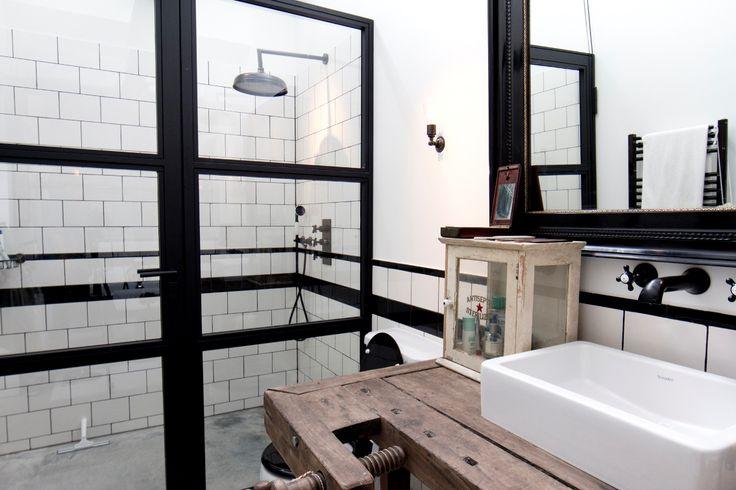 Loft badkamer met ruwe materialen zoals een werkbank als wastafel.