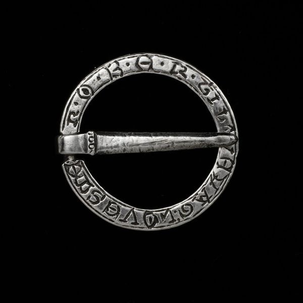 England, Britain (made) Date:ca. 1250-1350 (made) Artist/Maker:unknown (production) Materials and Techniques:Silver, engraved Ring brooch, silver. One one side engraved with an inscription in simple Lombardic letters 'R.O.B.E.R.T.I LOVE YAG: LOVES ME' (Robert I love (you?). On the other side similarly engraved with the inscription 'IHESUS NAZARENUS REX IUD' (Jesus of Nazareth, King of the Jews).