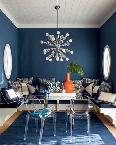 """FAUX PAS: This beautiful deep blue breakfast room with parallel round windows, sunbrella cushions, bold light fixture and great seat brackets has a common flaw & one of my pet peeves - a dining bench built too high to sit on and still have enough leg room under a 30"""" table. Even without the cushions the bench is high. Remember the finished bench height including the cushion should be the same height as a comfortable dining chair."""
