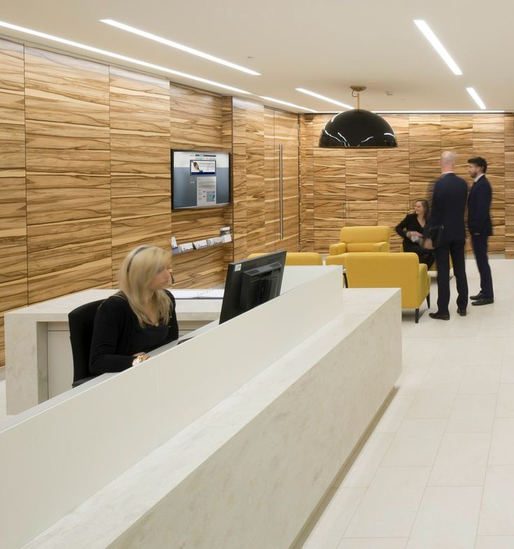 Office Reception Area >> Wood panelled wall >> We love the textured wall of wood panels  in this office fit out. The textured wood contrasts with the smooth white marble reception desk and white tiled floors. This cool reception space also features an LCD large format display screen to show news and updates to visitors or staff.