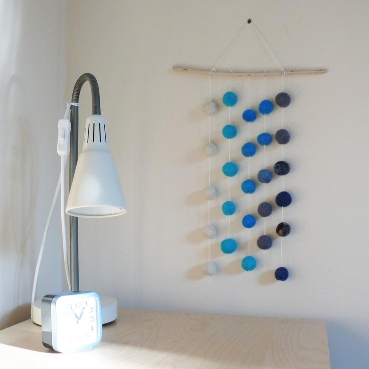 Zimní kuličky  Závěs tvořený 27 plstěnými kuličkami v barvách od bílé, přes tyrkysovou po tmavě modrou. Jsou zavěšené na bílém provázku, upevněné na krásném klacíku uřízlého z keře zlatého deště. Délka od klacíku po nejspodnějších kuličku cca 35 cm.