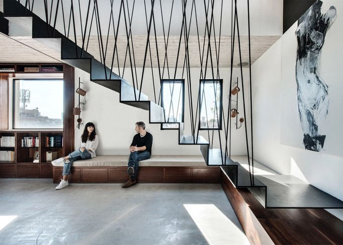 A folded steel staircase supported by criss-crossing rods connects the two levels of this duplex apartment in Tel Aviv, recently renovated by local studio Toledano Architects. The sculptural staircase becomes the centrepiece of the home, which was redesigned by Toledano Architects to better suit the needs of a young family. It is suspended from the walls and ceiling, meaning it doesn't touch th..