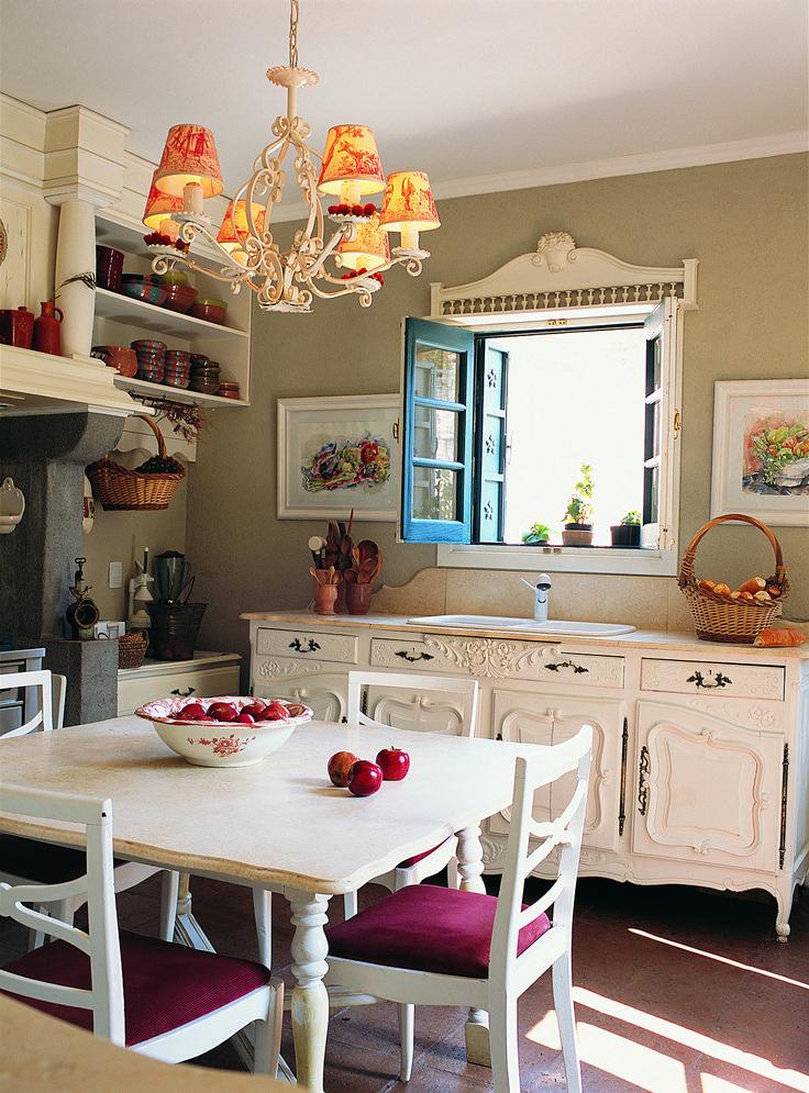 Cocina de una casa en Córdoba con muebles antiguos laqueados en blanco. Además, lámpara de techo y sillas con detalles en violeta.