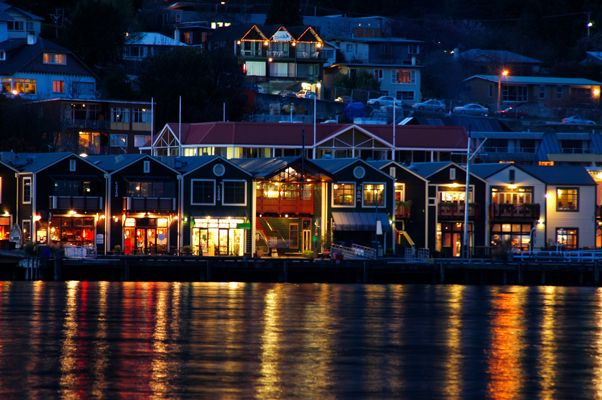 Queenstown's Steamer Wharf under night lights, with lake Wakatipu in foreground... Goodstays brand photo by Mark Evans.