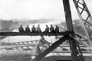 Schilders op de Hef in 1932 gefotografeerd door de Rotterdamse fotograaf K. in 't Veld. De foto is een beetje te vergelijken met de beroemde foto Lunchtime atop a Skyscraper van Charles Ebbets waarop elf mannen lunchen op een stalen balk van een wolkenkrabber in New York zitten. De foto komt uit het archief van Spaarnestad.