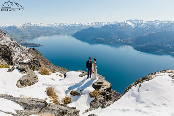 bride and groom stand on The Ledge above Lake Wakatipu. Destination Heli weddings Queenstown.