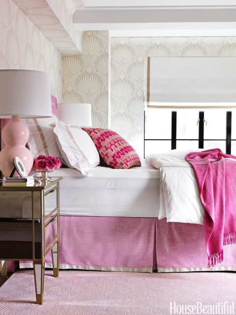 Pink adds soothing femininity to the master bedroom, where a bed skirt and headboard are in Manuel Canovas's Brasilia. The mirrored bedside table from Pottery Barn sparkles against Farrow & Ball's Lotus wallpaper.