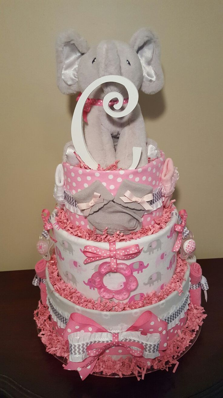 Adorable!!! Pink and gray baby girl elephant diaper cake. Perfect centerpiece gift loaded with 4 Carter's receiving blankets,  3 pair of Carter's socks, 6 washcloths,  2 MAM pacifiers, 1 teether, Gund musical elephant, and the initial letter of your choice.  68 pampers swaddlers.  visit my Facebook page Simply Showers for more pics and orders.