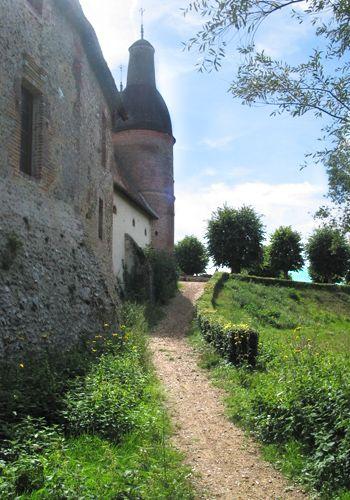 Chemin qui longe les anciennes écuries et les anciennes douves du site jusqu'au porche d'entrée.