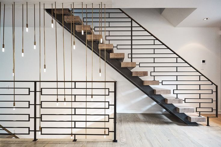 This floating staircase in a Philadelphia home features geometrically patterned steel balusters and wood treads.