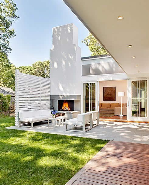 backyard love this entertaining #courtyard with it's white chimney and white seating, shuttered wall at the back and LUSCIOUS green green grass. Looks like a great indoor/outdoor flow.