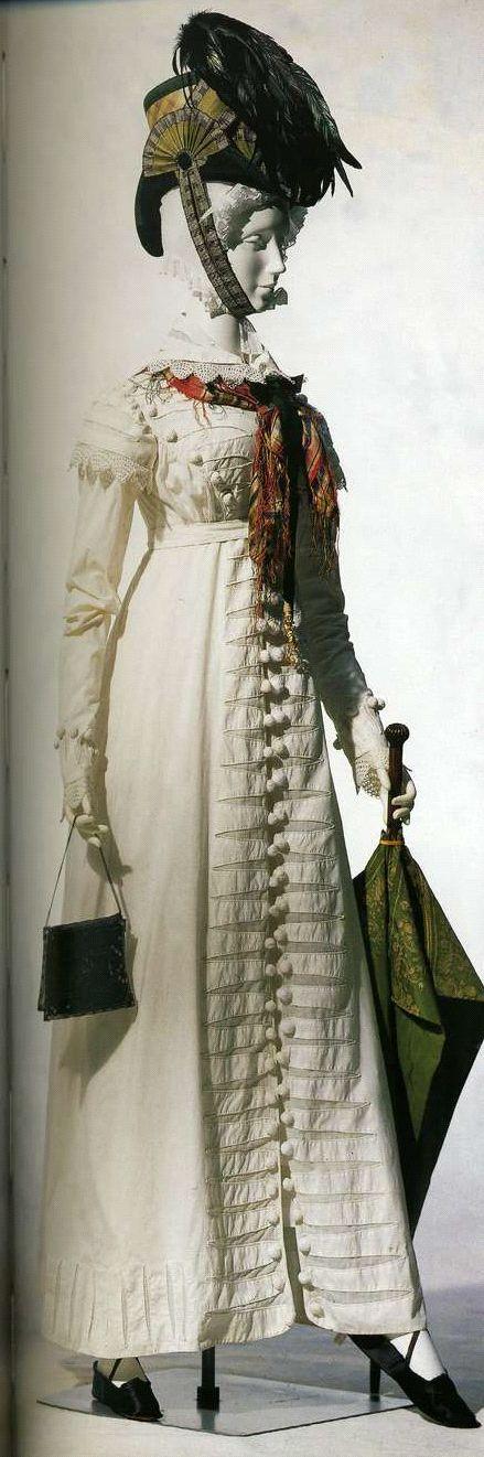 Редингот (a la Hussarde). Около 1815. Белый хлопок полотняного переплетения, отделка кантом и помпонами в гусарском стиле, сумочка из металлической сетки с серебряной застежкой.