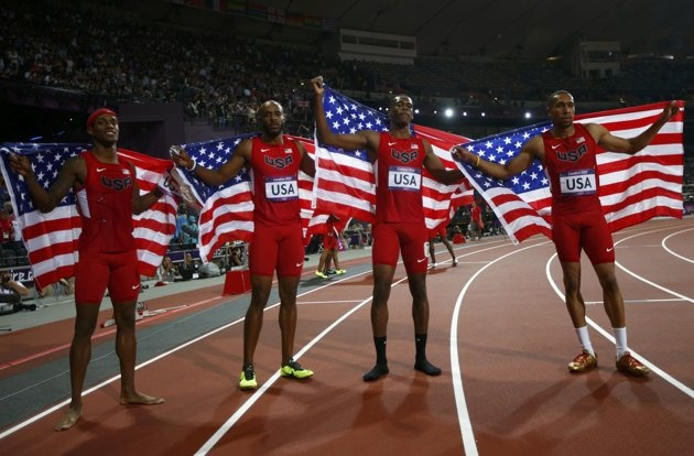 Tony McQuay (L-R), Angelo Taylor, Joshua Mance and Bryshon Nellum of the U.S. pose with their national flags after the men's 4x400m relay final during the London 2012 Olympic Games at the Olympic Stadium August 10, 2012. The U.S. won the silver medal in the event. REUTERS/Kai Pfaffenbach