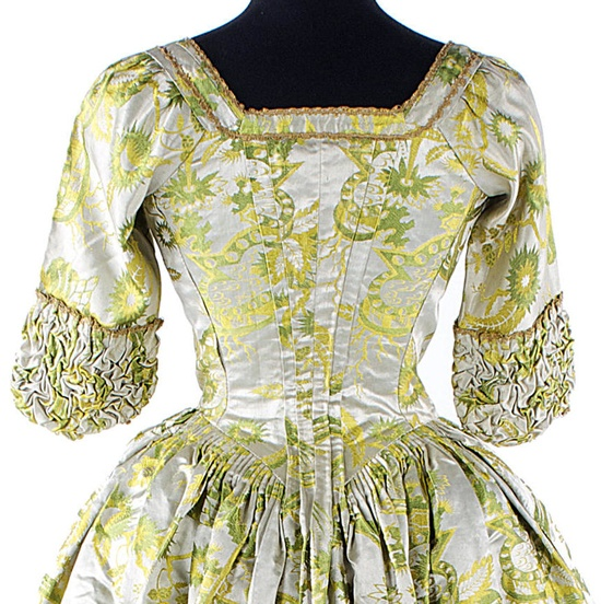 "Detail back view of brocade of bright yellow, green and ivory silk satin open robe, ca. 1740s, England. Provenance: 'Lady Frances Clemant's Wedding Dress"". Bonhams"