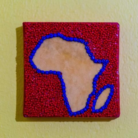Shop: Canvas D'Afrique - Red. This Africa is partially beaded on canvas in red and blue with a center of a light orange fabric. Size: 10cm x 10cm. By Boudoir D'Afrique
