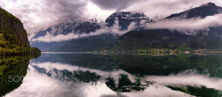Calm Fjord Reflections - The cloudy mountains reflect nicely in a calm Hardangerfjord. This is Norway!