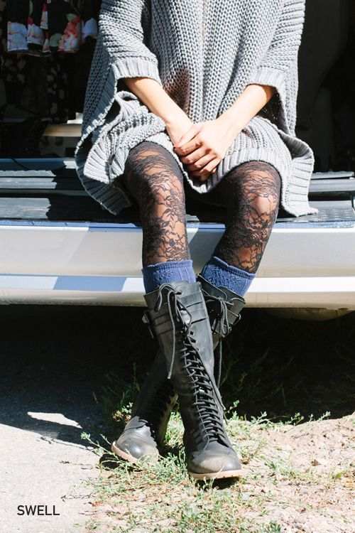 Lace up tall combat boots and lace tights with knit knee socks and an oversized knit.
