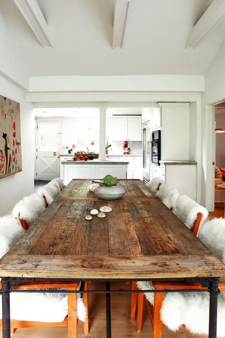 this all white dining room features a reclaimed wood dining table and easy access to: long wood dining table