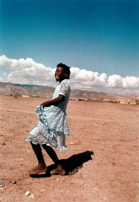 Young girl dancing in her blue lace dress belies the sinister poverty and violence that reside in the dusty, dried-out streets of Rabato, a slum just outside Gonaives, Haiti. Rabato is a scene of regular political protest and is thus the target of numerous slaughters and attacks on its citizens. 1990