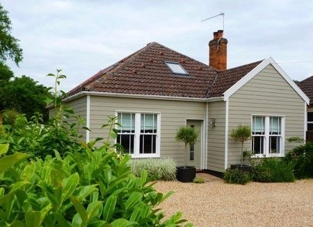Detached refurbished bungalow with HardiePlank cladding in soft green colour