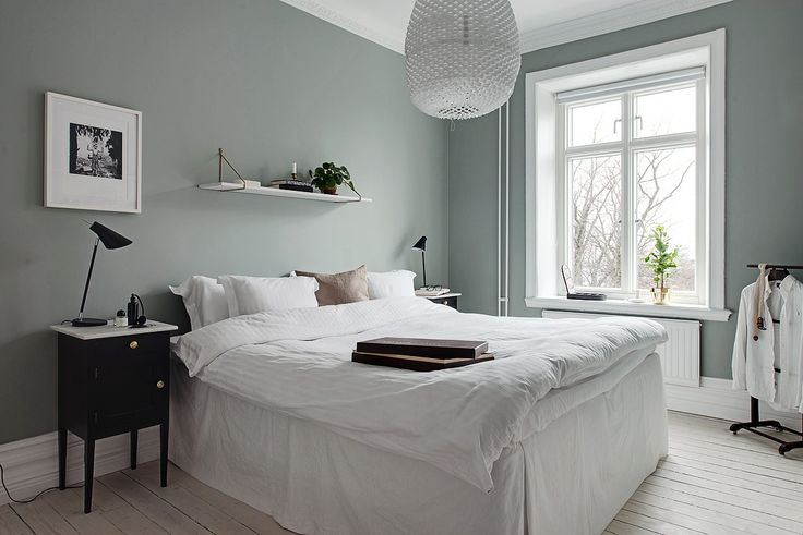 Bedroom with pale green walls and white pigmented floor. Black bedside tables with bedside lamps by Louis Poulsen and white bed.