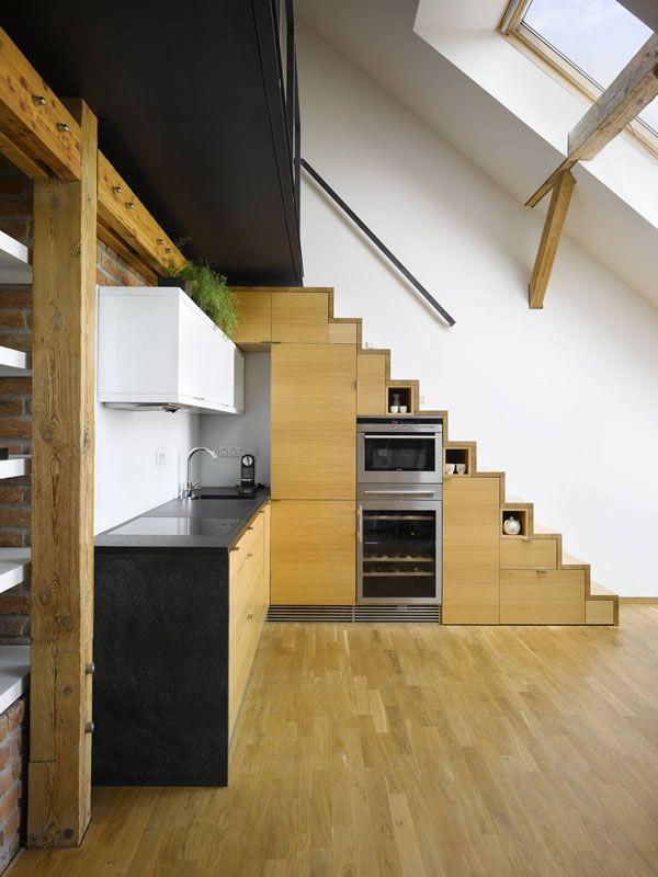 Usar el hueco de las escaleras para meter la nevera, el horno, el microondas y algunos armarios es un genial aprovechamiento de un espacio que, de otra forma, sería inútil.