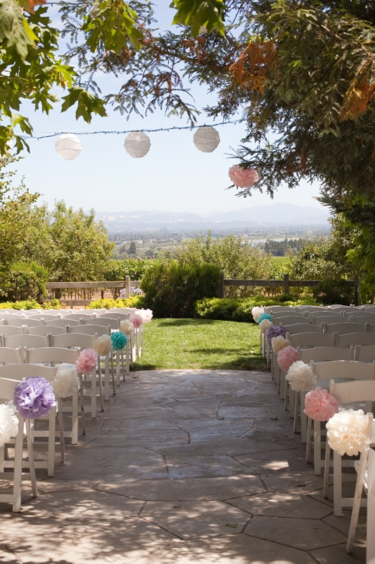 Pastel paper pom poms look soft and pretty against the cream chairs and ivory lanterns above, sometimes less is more.