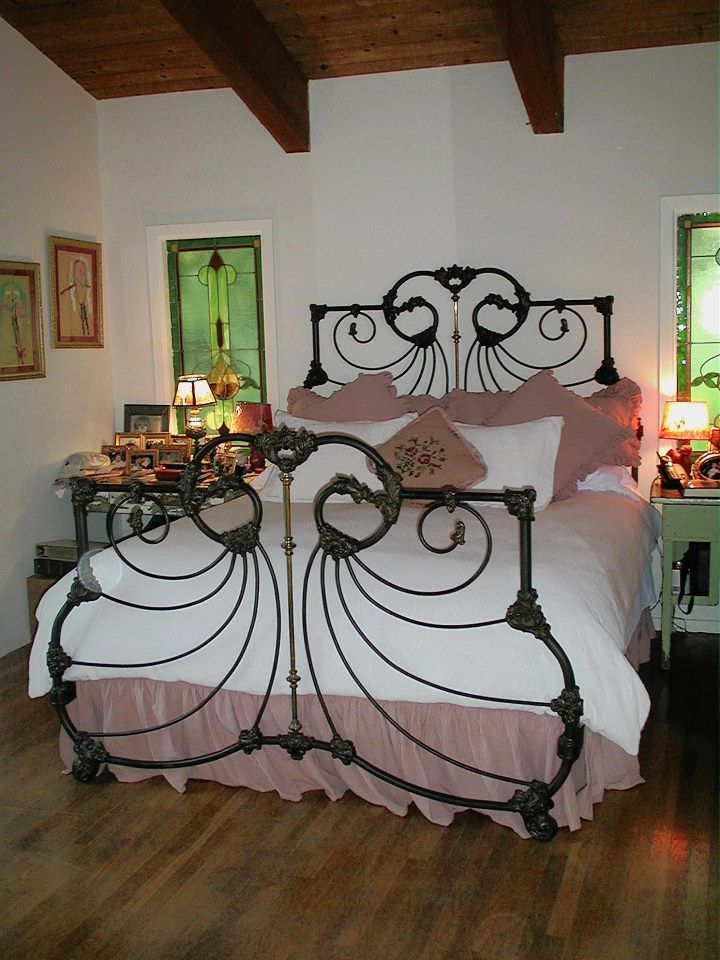 this french curve side antique iron bed has been flawlessly converted to a modern king size