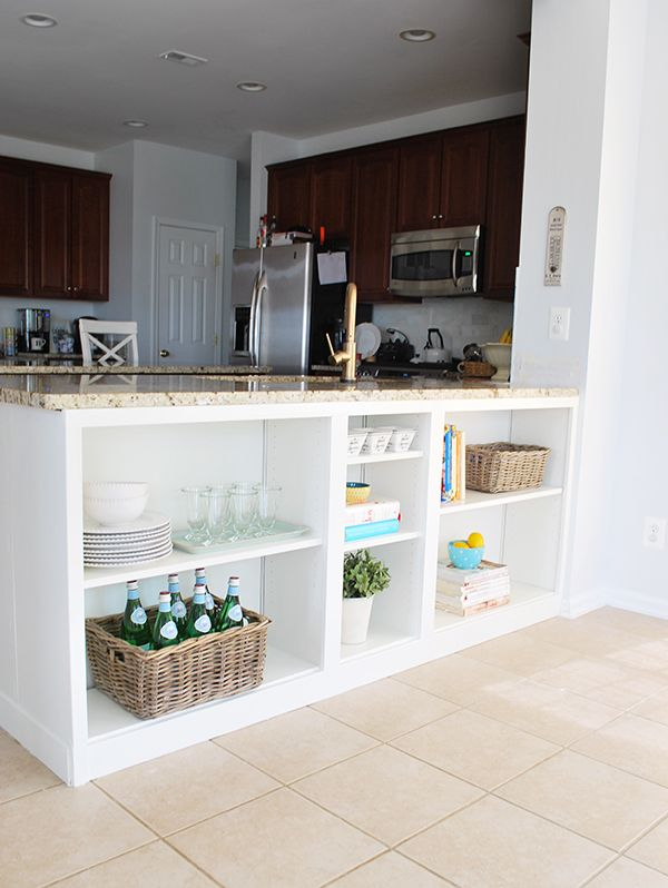 "This was unused space under a counter, they filled it in with IKEA Billy Bookcases ""hacked"" to make it look like built-in kitchen shelving. Puts shelves right near the table, so smart! Easy project with tutorial."