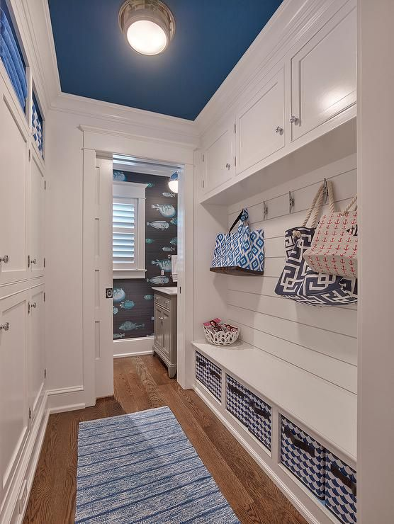 Galley style mudroom features a blue ceiling lined with a polished nickel flush mount illuminating a long built-in bench fitted with open shelving lined with white and blue bins with leather handles accented with a shiplap backsplash with overhead cabinets.