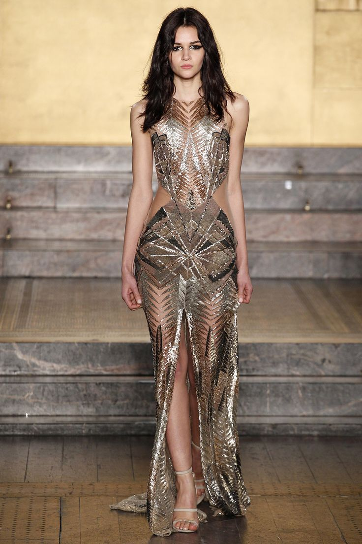 LFW '16: Glittering gold gown with geometric pattern, sheer mesh sides and front split from Julien Macdonald's Fall 2016 RTW Collection...x