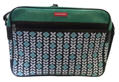 Een leuke schoudertas uit de Skyline collectie met een retro bloemenmotiefje.  De tas heeft een ruim binnenvak met een apart zijvak en nog een klein vakje dat sluit met een rits.  Met een lange schouderriem.
