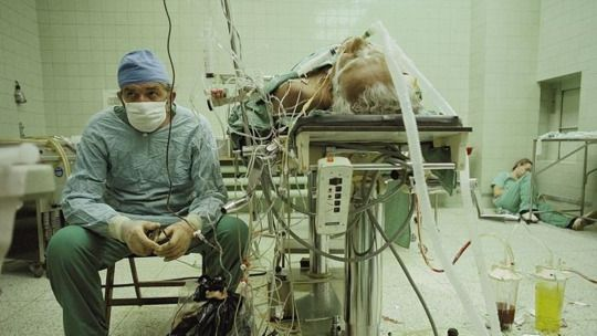 Dr. Religa monitors his patient's vitals after a 23-hour-long successful heart transplant. His assistant is sleeping in the corner. Poland, 1987.