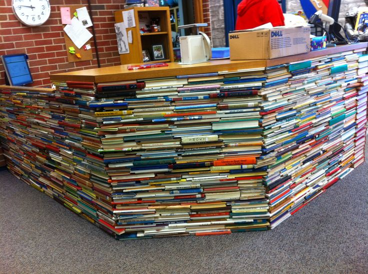 I still like this idea even if it won't be used in the new library.      Kent took books that were being thrown out at his school library and cut both ends off with his miter saw.  He then glued them to the surface of this massive desk in his elementary school library to for a faux finish to make it look like a giant stack of books.  It took hundreds of books and a lot of noise.